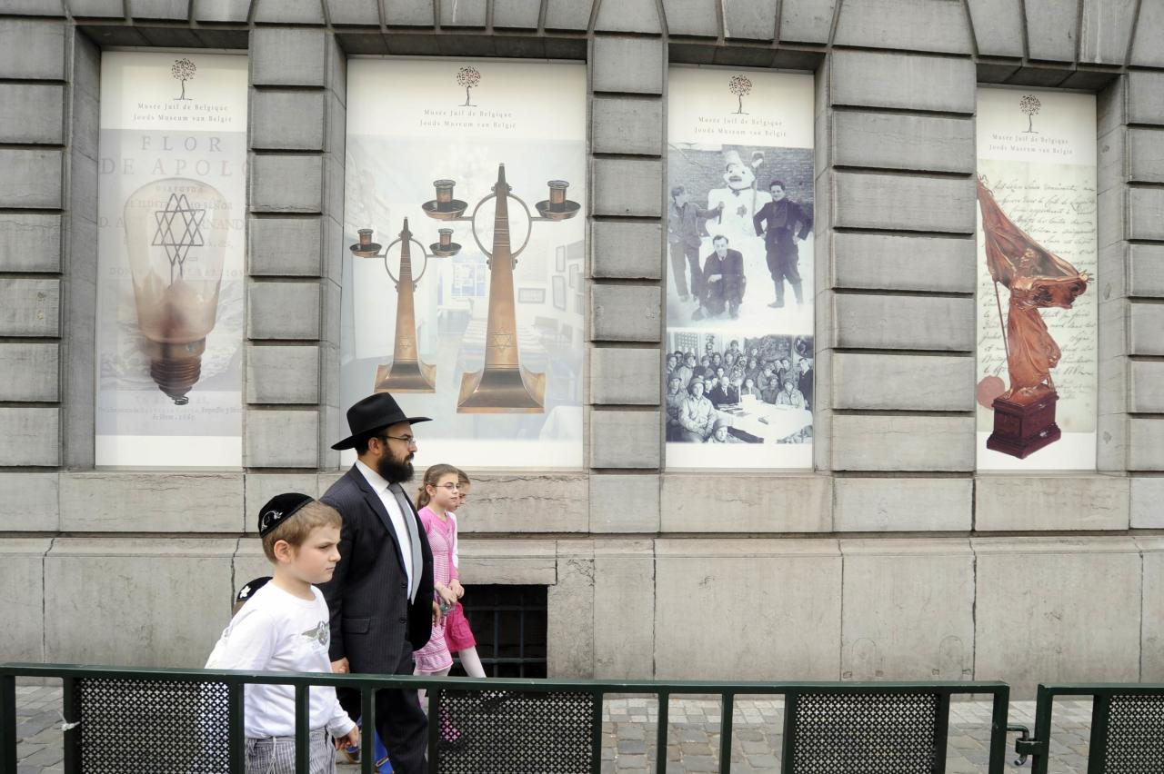 A family walks in front of the Jewish Museum, site of a shooting in central Brussels May 25, 2014. Belgian police were hunting on Sunday for an assailant who shot dead three people at the Jewish Museum in Brussels, and French authorities tightened security at Jewish sites following another attack that prompted fears of a rise in anti-Semitism. REUTERS/Eric Vidal (BELGIUM - Tags: CRIME LAW)