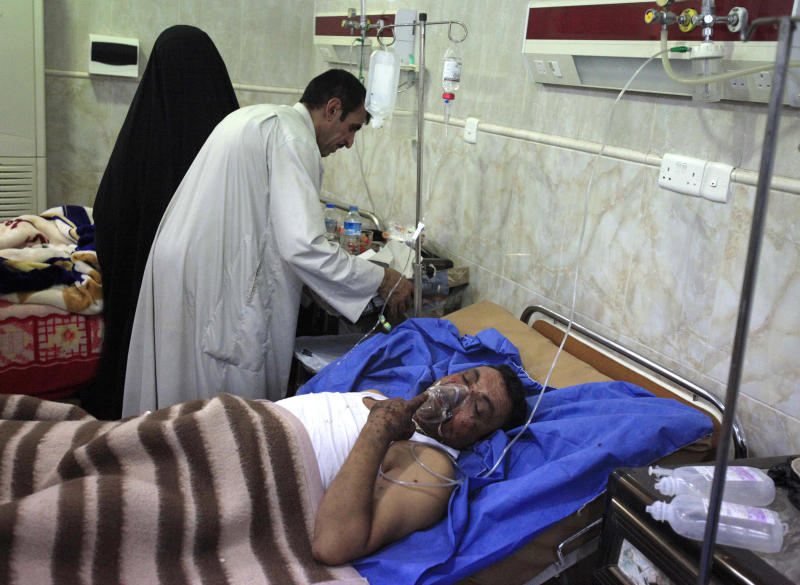 An injured victim receives treatment at a hospital after a car bomb attack outside Kut, 100 miles (160 kilometers) southeast of Baghdad, Iraq, Sunday, Jun 16, 2013. Most of the car bombs hit Shiite-majority areas and were the cause of most of the casualties, killing tens. The blasts hit half a dozen cities and towns in the south and center of the country. (AP Photo/Karim Kadim)
