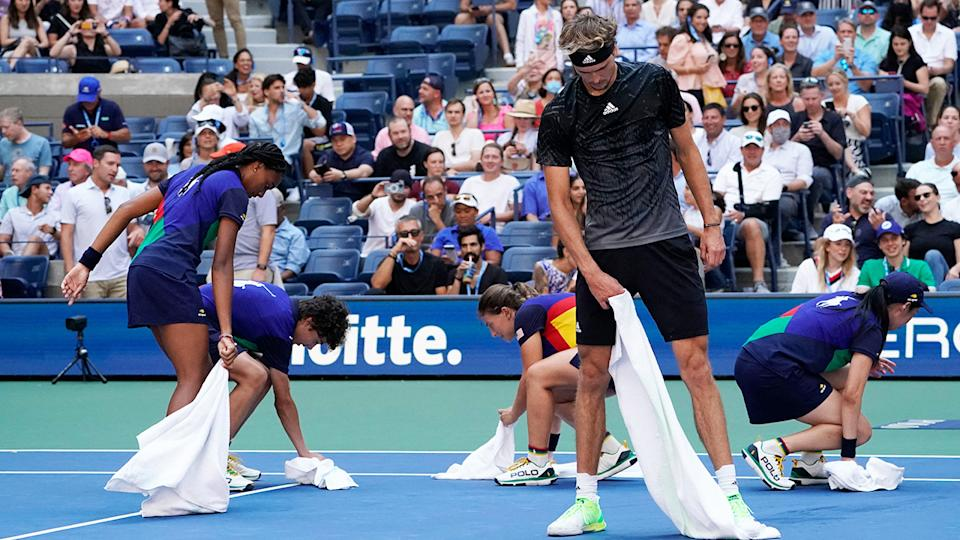 Alexander Zverev, pictured here helping dry the court during his US Open quarter-final clash with Lloyd Harris.