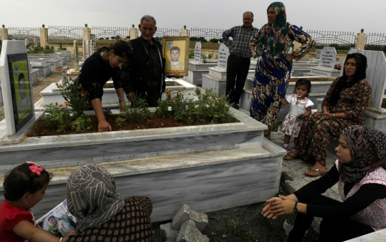 Syrian Kurds visit graves of loved ones at a cemetery in the northern town of Kobane on May 28, 2018