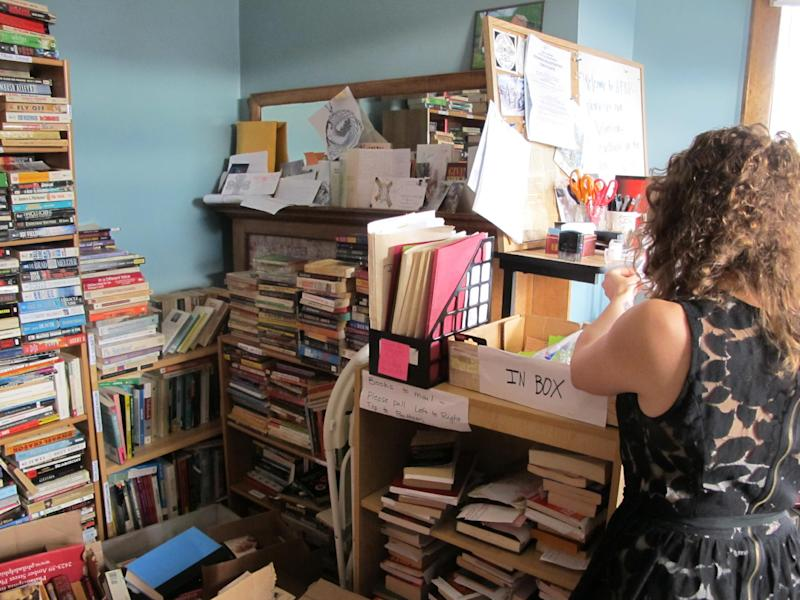 Used books fill every available space in the office of the Appalachian Prison Book Project in Morgantown, W.Va., on Nov. 13, 2012, as outreach coordinator Dominique Bruno looks at unopened requests. The volunteer program has so far shipped more than 11,000 free, used books to prisoners in West Virginia, Virginia, Kentucky, Maryland, Ohio and Tennessee. (AP Photo/Vicki Smith)