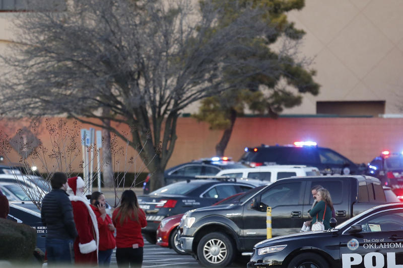 Bystanders, including one dressed as Santa Claus, watch as police clear Penn Square Mall following a shooting Thursday, Dec. 19, 2019, in Oklahoma City. One person was shot at the mall during what police are calling a disturbance involving two people. (AP Photo/Sue Ogrocki)