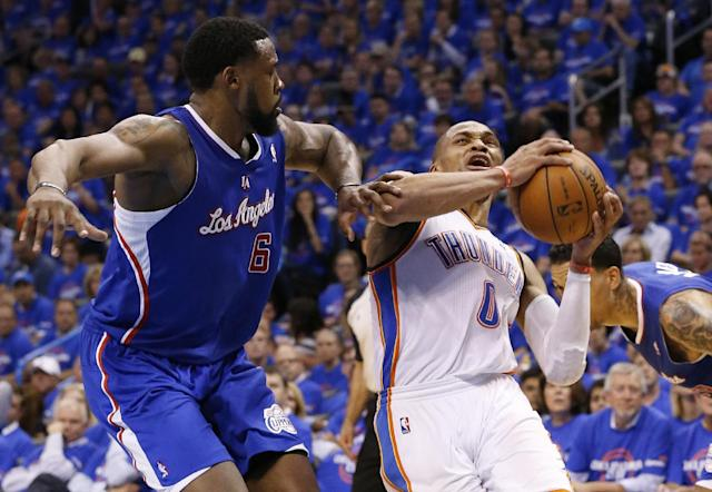 Oklahoma City Thunder guard Russell Westbrook (0) is fouled by Los Angeles Clippers center DeAndre Jordan (6) in the third quarter of Game 1 of the Western Conference semifinal NBA basketball playoff series in Oklahoma City, Monday, May 5, 2014. Los Angeles won 122-105. (AP Photo/Sue Ogrocki)