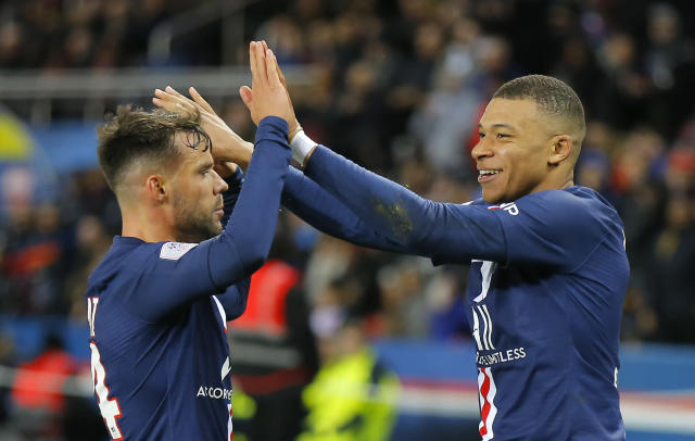 PSG's Kylian Mbappe, right, celebrates with teammate Juan Bernat after scoring his side's fourth goal during the French League One soccer match between Paris-Saint-Germain and Dijon, at the Parc des Princes stadium in Paris, France, Saturday, Feb. 29, 2020. (AP Photo/Michel Euler)