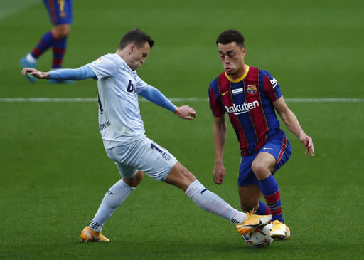 Valencia's Denis Cheryshev, left vies for the ball with Barcelona's Sergino Dest during the Spanish La Liga soccer match between Barcelona and Valencia at the Camp Nou stadium in Barcelona, Spain, Saturday, Dec. 19, 2020. (AP Photo/Joan Monfort)