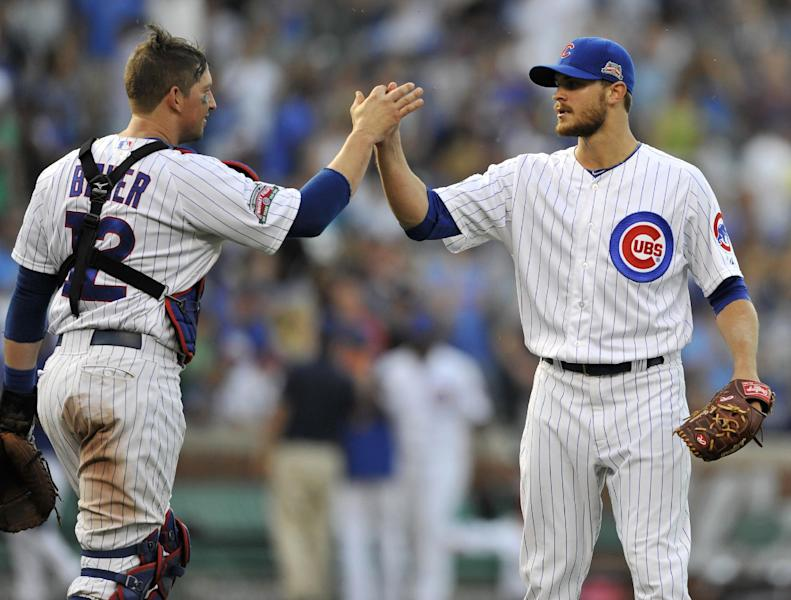 Chicago Cubs closing pitcher Justin Grimm right, celebrates with catcher John Baker (12) after the Cubs defeated the Washington Nationals 7-2 during a baseball game in Chicago, Friday, June 27, 2014. (AP Photo/Paul Beaty)