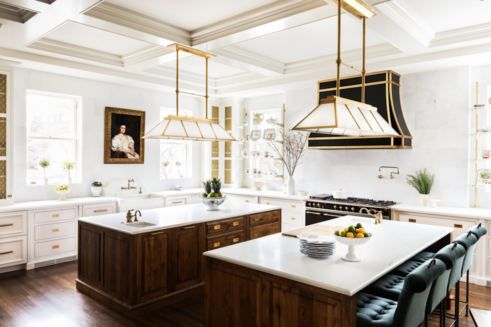 """<p>The kitchen in <a href=""""https://www.veranda.com/decorating-ideas/a29416571/shazalynn-cavin-winfrey-greenwich-home-tour/"""" rel=""""nofollow noopener"""" target=""""_blank"""" data-ylk=""""slk:this Connecticut house"""" class=""""link rapid-noclick-resp"""">this Connecticut house</a> designed by <a href=""""https://www.scwinteriors.com/"""" rel=""""nofollow noopener"""" target=""""_blank"""" data-ylk=""""slk:Shazalynn Cavin-Winfrey"""" class=""""link rapid-noclick-resp"""">Shazalynn Cavin-Winfrey</a> is luxe in every sense of the word, from the marble walls and Lacanche range to the oil portraits, brass details, and mohair-upholsted counter stools (by <a href=""""https://www.hollyhunt.com/"""" rel=""""nofollow noopener"""" target=""""_blank"""" data-ylk=""""slk:Holly Hunt"""" class=""""link rapid-noclick-resp"""">Holly Hunt </a>for <a href=""""https://www.bradlee.net/"""" rel=""""nofollow noopener"""" target=""""_blank"""" data-ylk=""""slk:Bradlee USA"""" class=""""link rapid-noclick-resp"""">Bradlee USA</a>). </p><p>The double islands, which feature dark wood finish that helps them stand out from the white perimeter cabinets, make entertaining a breeze: One is outfitted with an ice machine, sink, and beverage drawer, making it easy to stand in as a bar. A pair of corner cabinets fitted with metal mesh provide vertical storage and echo the other brass elements throughout the space.</p>"""