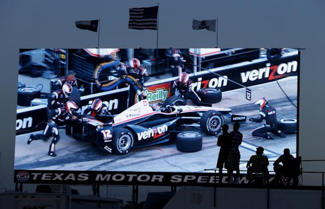 Race fans watch a video screen that shows Will Power, of Australia, pitting during the IndyCar auto race at Texas Motor Speedway in Fort Worth, Texas, Saturday, June 7, 2014. (AP Photo/Larry Papke)