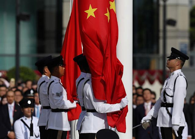 <p>The Chinese (R) and Hong Kong (L) flags are raised during a ceremony at Golden Bauhinia Square in Hong Kong on July 1, 2017 to celebrate the 20th anniversary of the establishment of the Hong Kong Special Administrative Region (HKSAR). (Photo: Dale de la Rey/AFP/Getty Images) </p>
