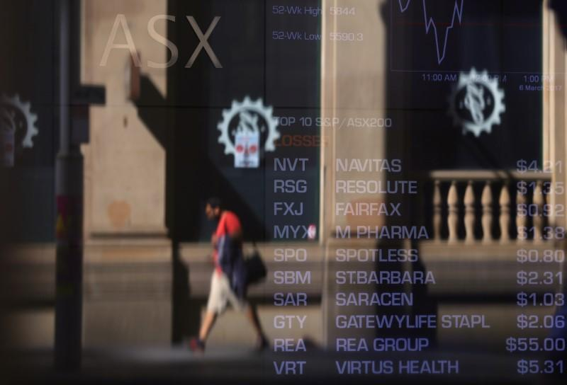 A pedestrian is reflected in a window displaying a board with stock prices at the Australian Securities Exchange (ASX) in Sydney
