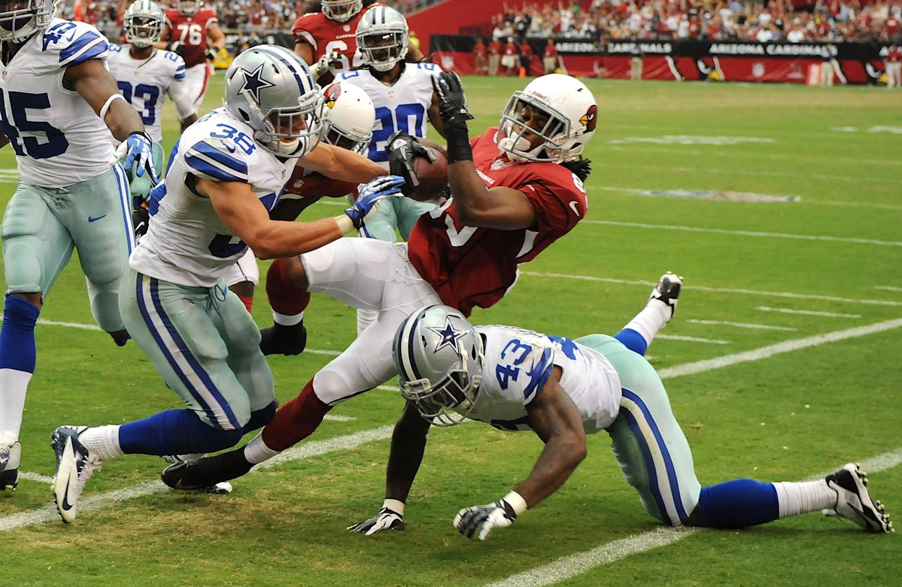 GLENDALE, AZ - AUGUST 17: Charles Hawkins #89 of the Arizona Cardinals gets knocked out of bounds by Jakar Hamilton #43 and Jeff Heath #38 of the Dallas Cowboys at University of Phoenix Stadium on August 17, 2013 in Glendale, Arizona. Cardinals won 12-7. (Photo by Norm Hall/Getty Images)