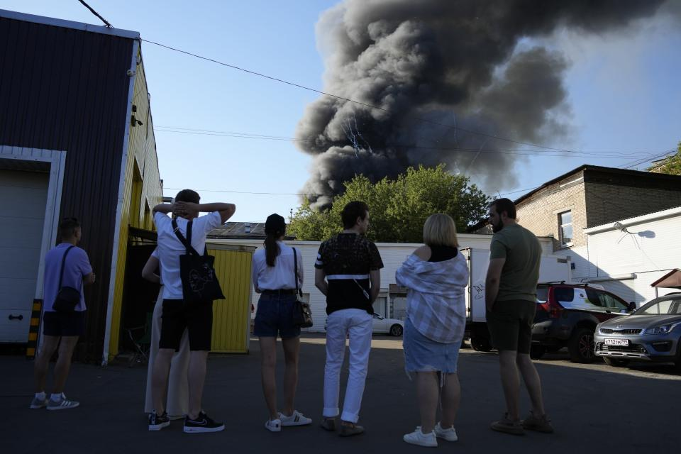 People watch as smoke rises from a pyrotechnics warehouse in Moscow, Russia, Saturday, June 19, 2021. A large fire broke out at a fireworks depot in the center of Moscow. The fire is raging at the area of 500 square meters, Russia emergency services said in the statement. (AP Photo/Pavel Golovkin)