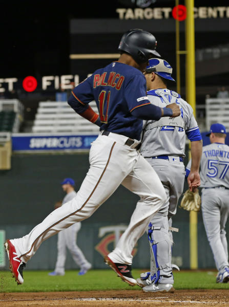 Minnesota Twins' Jorge Polanco, left, scores on a double by Nelson Cruz off Toronto Blue Jays pitcher Trent Thornton, right, in the third inning of a baseball game Wednesday, April 17, 2019, in Minneapolis. (AP Photo/Jim Mone)