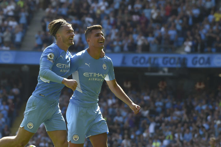 Manchester City's Rodrigo, right, celebrates after scoring his side's fourth goal during the English Premier League soccer match between Manchester City and Arsenal at Etihad stadium in Manchester, England, Saturday, Aug. 28, 2021. (AP Photo/Rui Vieira)