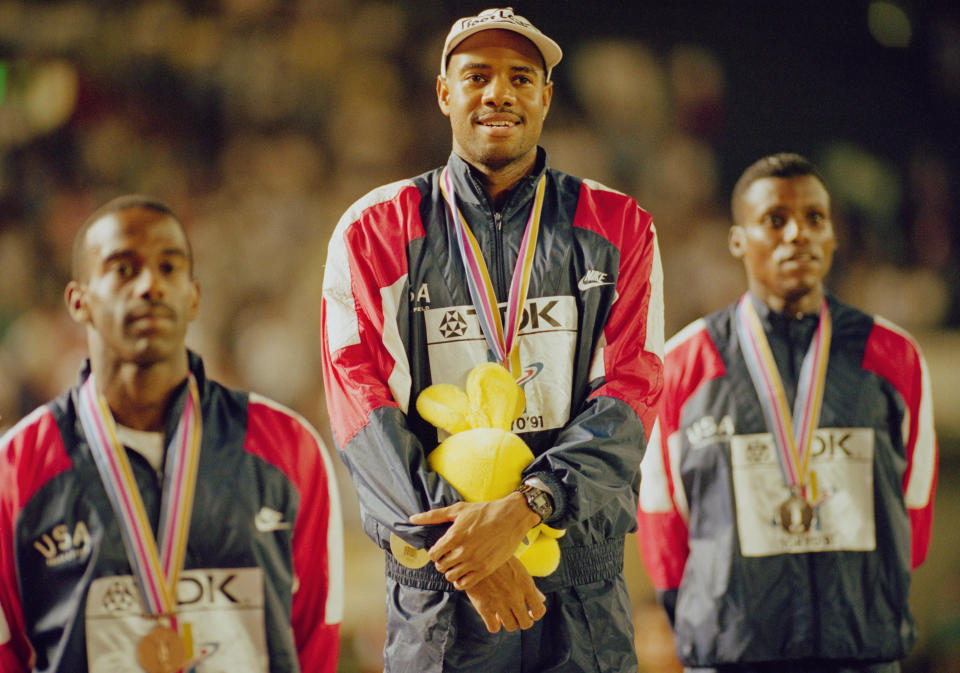 Mike Powell of the United State celebrates on the podium  with silver medallist Carl Lewis (R) and bronze medallist Larry Myricks (L) after making his world record leap during the Long Jump event at the IAAF World Athletic Championships on 30th August 1991 at the Olympic Stadium in Tokyo, Japan. Powell broke Bob Beamon's 23-year-old long jump world record by 5 cm (2 inches), leaping 8.95 m (29 ft 4 in). (Photo by Mike Powell/Getty Images)