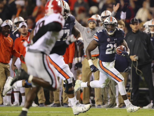 "FILE – In this Nov. 11, 2017, file photo, Auburn running back <a class=""link rapid-noclick-resp"" href=""/ncaaf/players/255521/"" data-ylk=""slk:Kerryon Johnson"">Kerryon Johnson</a>, right, breaks away from Georgia defenders for a touchdown run. (Curtis Compton/Atlanta Journal-Constitution via AP, File)"