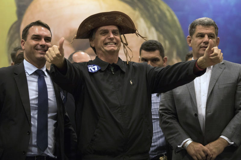 FILE - In this Oct. 11, 2018 file photo, presidential candidate Jair Bolsonaro flashes two thumbs up during a press conference in Rio de Janeiro, Brazil. The success of Bolsonaro's campaign caught many by surprise as the far-right congressman tapped into an anti-establishment wave. He focused on cracking down on crime and wooing the business community with a promise to enact liberal economic policies. (AP Photo/Leo Correa)
