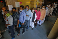 Indians wearing face masks as precaution against COVID-19, stand in queue to cast their vote for local body elections in Ahmedabad, India, Sunday, Feb. 21, 2021. (AP Photo/Ajit Solanki)