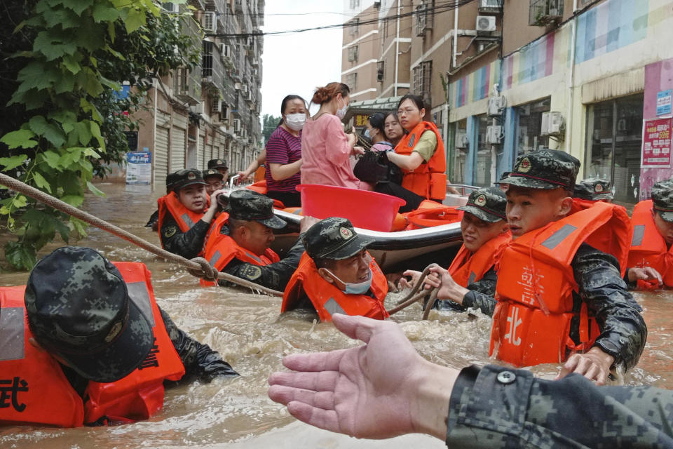 FILE - In this Thursday, Aug. 12, 2021 file photo, paramilitary police work to evacuate people trapped in a flooded area in Suizhou in central China's Hubei Province. Flooding in central China continued to cause havoc in both cities and rural areas. According to a United Nations report released on Tuesday, Oct. 5, 2021, much of the world is unprepared for the floods, hurricanes and droughts expected to worsen with climate change and urgently needs better warning systems to avert water-related disasters. (Chinatopix via AP)
