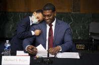 Administrator of the Environmental Protection Agency nominee Michael Regan is hugged by his son, Matthew, after his confirmation hearing before the Senate Environment and Public Works committee on Capitol Hill in Washington, Wednesday, Feb. 3, 2021. (Caroline Brehman/Pool via AP)