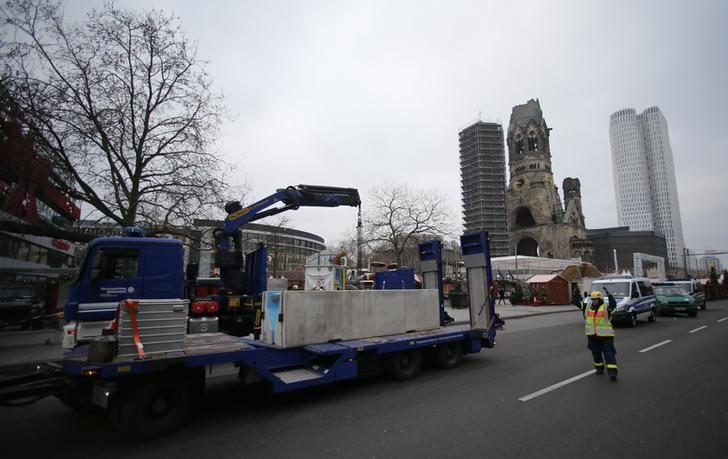 Workers place concrete barriers outside the Christmas market at Breitscheid square in Berlin