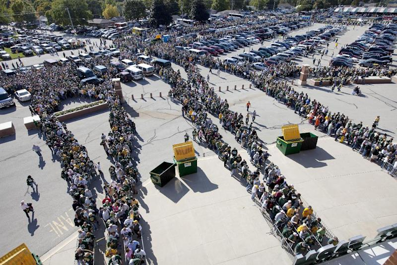 FILE - In this Oct. 2, 2011, file photo, fans wait at a security checkpoint as they enter Lambeau Field for an NFL football game between the Denver Broncos and the Green Bay Packers in Green Bay, Wis. The NFL is tightening stadium security starting this preseason, limiting the size and type of bags fans can bring to the game. The restrictions are designed to enhance security while speeding up entry into stadiums. (AP Photo/Mike Roemer, File)