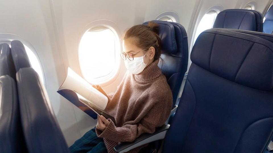 A young woman wearing face mask is traveling on airplane , New normal travel after covid-19 pandemic