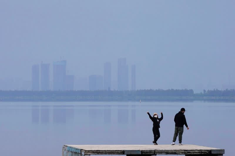 FILE PHOTO: Woman wearing a face mask dances on the East Lake in Wuhan