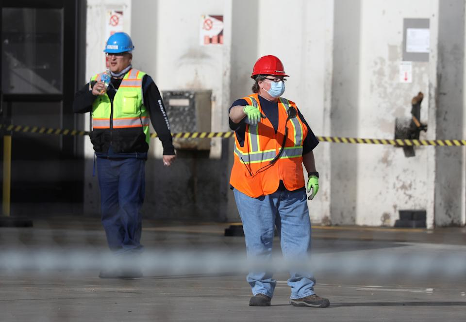 Employees wear face masks at a meat packing plant