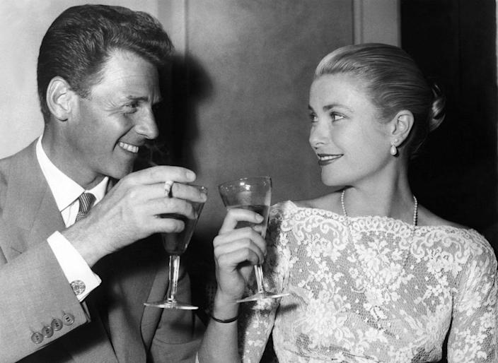 <p>Kelly clinks glasses with French actor Jean-Pierre Aumont, while attending a Hollywood event in 1955. The actress looks gracious as ever in a long-sleeve lace dress and pearls. </p>