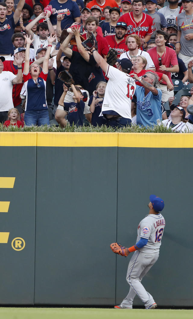 New York Mets center fielder Juan Lagares (12) watches as fans try to catch a ball hit for a two-run home run by Atlanta Braves first baseman Freddie Freeman (5) in the first inning of a baseball game Wednesday, June 19, 2019, in Atlanta. (AP Photo/John Bazemore)