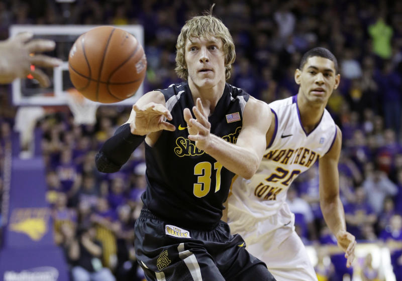 Wichita State guard Ron Baker, left, passes in front of Northern Iowa guard Jeremy Morgan during the first half of an NCAA college basketball game on Saturday, Feb. 8, 2014, in Cedar Falls, Iowa. (AP Photo/Charlie Neibergall)