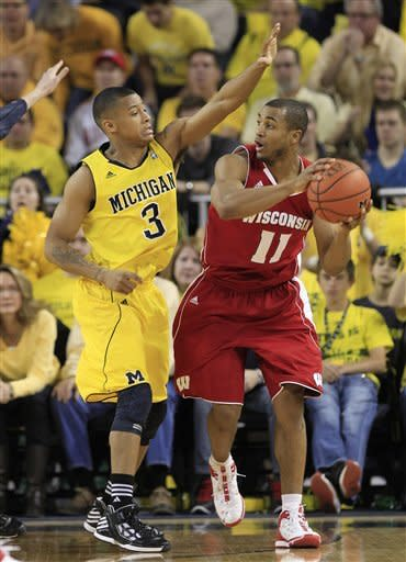 Wisconsin guard Jordan Taylor (11) looks to pass around Michigan guard Trey Burke (3) during the first half of an NCAA college basketball game in Ann Arbor, Mich., Sunday, Jan. 8, 2012. (AP Photo/Carlos Osorio)