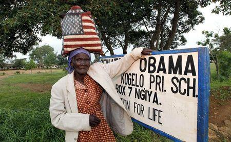 Rosa Anyango poses for a photograph as she carries a bag with the colors of the U.S. flag as she walks from the market near the ancestral home of U.S. President Barack Obama in Nyangoma village in Kogelo, west of Kenya's capital Nairobi, June 22, 2015. REUTERS/Thomas Mukoya