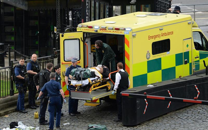 Khalid Masood is pictured being put into an ambulance just minutes after being shot by police. He later died. - Credit: PA