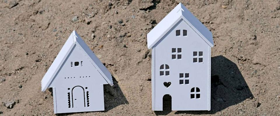 Plastic white house large and small or residential model in nature. Souvenir house with Windows. The concept of construction or capital investment. Mortgage or loan concept. Sand background.