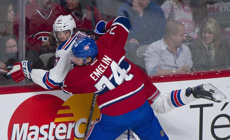 Montreal Canadiens' Alexei Emelin (74) checks New York Rangers' Benoit Pouliot into the boards during the first period of an NHL hockey game Saturday, Nov. 16, 2013, in Montreal. (AP Photo/The Canadian Press, Graham Hughes)