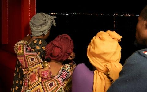 Rescued migrants look at lights on the island of Lampedusa from aboard the Ocean Viking - Credit: AP Photo/Renata Brito