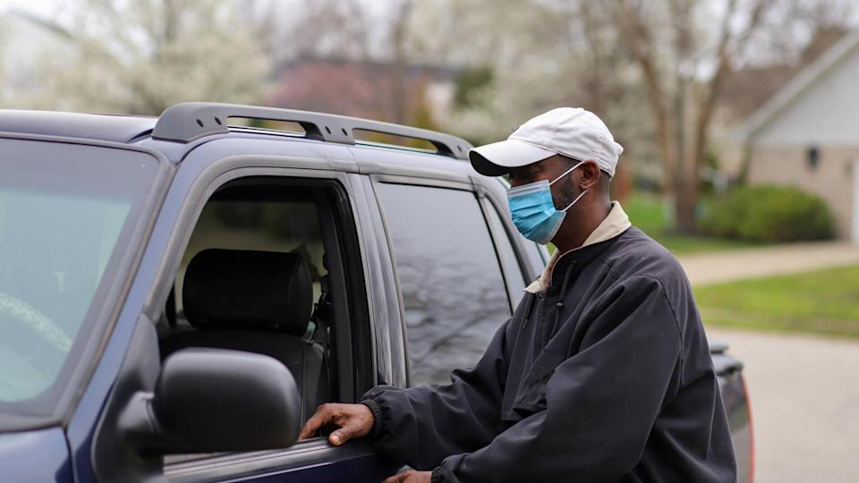 African-American man leaving in his truck wearing a mask to protect him from a virus infection.