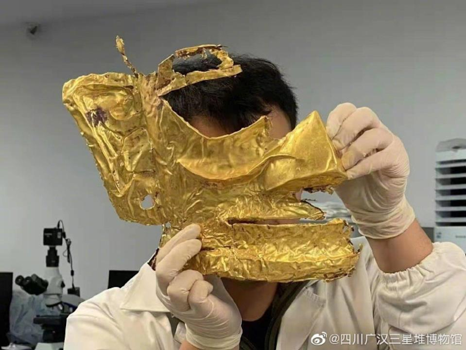 An archaeologist holds a newly excavated gold mask from the Sanxingdui site.