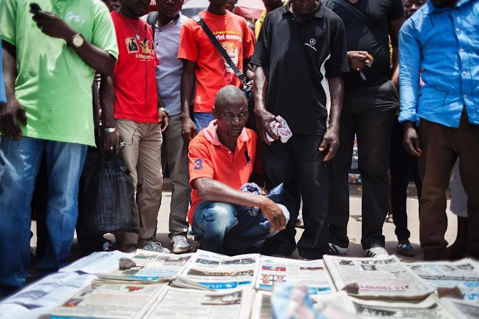 People gather in Brazzaville around a vendor selling copies of Congolese daily newspapers on March 21, 2016, a day after the presidential elections (AFP Photo/Eduardo Soteras)