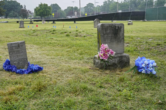 The headstones of Reuben Everett, left, and Eddie Lockard, right, victims of the Tulsa race massacre, are pictured with flowers Monday, May 31, 2021, at Oaklawn Cemetery in Tulsa, Okla., nearly 100 years after the massacre. Fencing has been erected and markers placed in the ground in preparation for the start of mapping, site preparation and excavations of Tulsa race massacre victims in mass graves beginning June 1, 2021. (AP Photo/Sue Ogrocki)