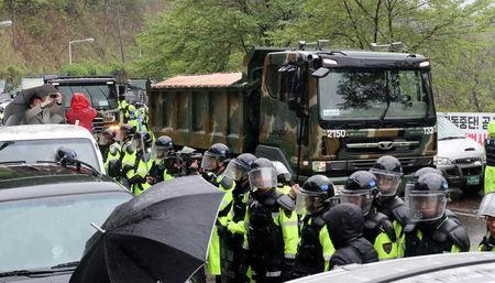 A military construction vehicle drives past residents (not pictured) taking part in an anti-THAAD (Terminal High Altitude Area Defense) protest in Seongju, South Korea, April 23, 2018. Yonhap via REUTERS