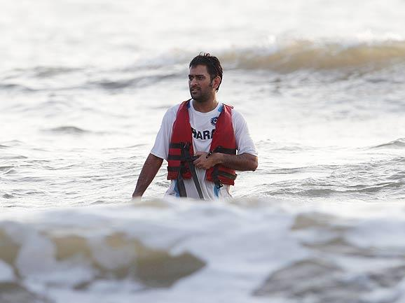 India's captain Mahendra Singh Dhoni walks back to the shore after spending time with wife Sakshi in the Arabian sea after India won the One-Day International match series against Australia by 1-0. (AP Photo)