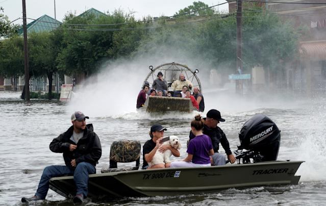 <p>People are rescued from flood waters from Hurricane Harvey on an air boat in Dickinson, Texas, Aug. 27, 2017. (Photo: Rick Wilking/Reuters) </p>