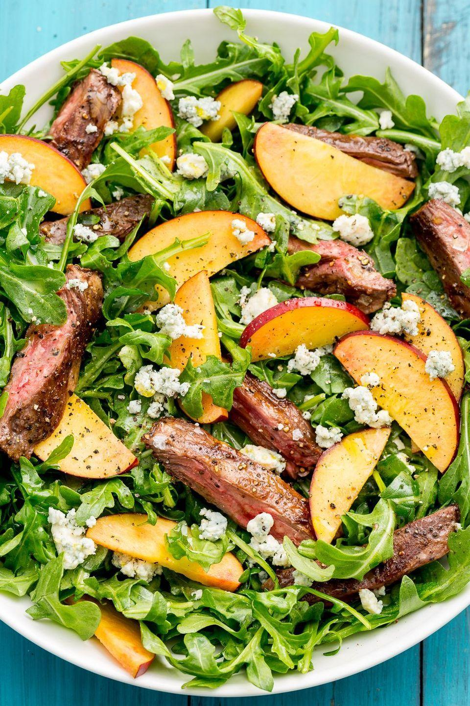"""<p>Peppery rocket is the perfect vessel for this savoury-sweet combo.</p><p>Get the <a href=""""https://www.delish.com/uk/cooking/recipes/a32998377/balsamic-grilled-steak-salad-with-peaches-recipe/"""" rel=""""nofollow noopener"""" target=""""_blank"""" data-ylk=""""slk:Balsamic Grilled Steak Salad with Peaches"""" class=""""link rapid-noclick-resp"""">Balsamic Grilled Steak Salad with Peaches</a> recipe. </p>"""