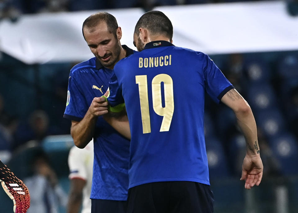 Italy's Giorgio Chiellini, left, gives the captain's armband to teammate Leonardo Bonucci before leaving the pitch during the Euro 2020 soccer championship group A match between Italy and Switzerland at Olympic stadium in Rome, Wednesday, June 16, 2021. (Andreas Solaro/Pool Photo via AP)