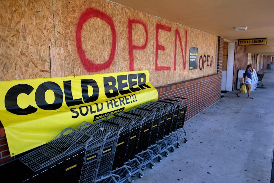 A woman exits a boarded up grocery store in Cocoa Beach, Florida.