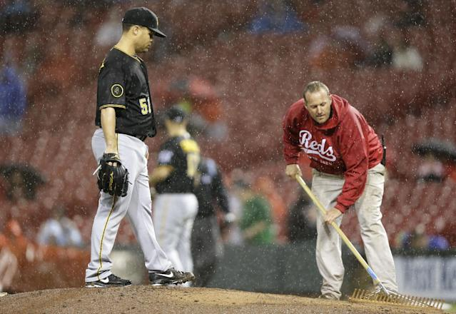 Pittsburgh Pirates starting pitcher Wandy Rodriguez (51) waits on the mound while a member of the Cincinnati Reds ground crew works on the mound in the fifth inning of a baseball game being played in the rain, Monday, April 14, 2014, in Cincinnati. (AP Photo/Al Behrman)