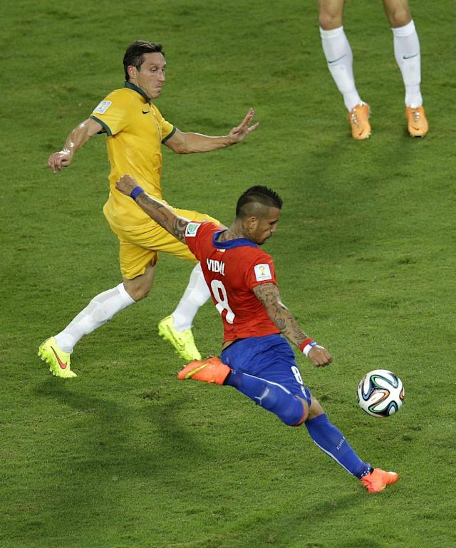 Chile's Arturo Vidal, right, shoots during the group B World Cup soccer match between Chile and Australia in the Arena Pantanal in Cuiaba, Brazil, Friday, June 13, 2014. (AP Photo/Michael Sohn)